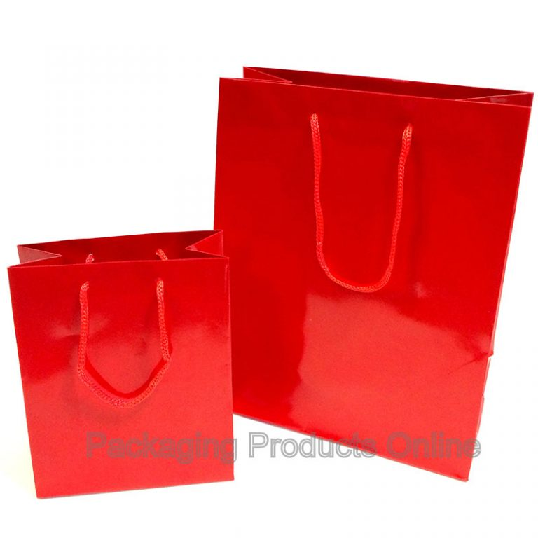 A small and medium sized glossy red gift bag with red cord handles.
