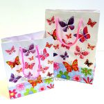 White gift bags with butterflies in all sizes and colours printed all over the bag.