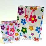 small and medium sized white gift bags printed with lots of daisy flowers in multiple colours